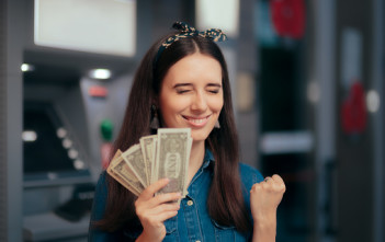 Girl having financial success holding dollars in front of a bank
